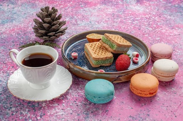 Deliziosi panini biscotto con gustosi macarons francesi e tazza di tè sulla scrivania rosa