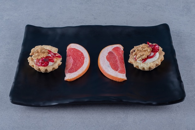 Delicious cookie with grapefruit slices on black plate over grey surface