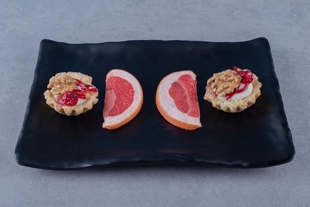 Вкусное печенье с ломтиками грейпфрута на черной тарелке над серой поверхностью