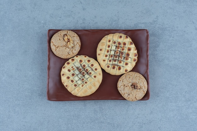 Delicious cookies on brown plate over grey. top view.