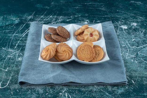 Biscotti deliziosi in un piatto su un asciugamano, sul tavolo blu.
