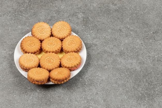 Вкусное печенье с кремом на белой тарелке