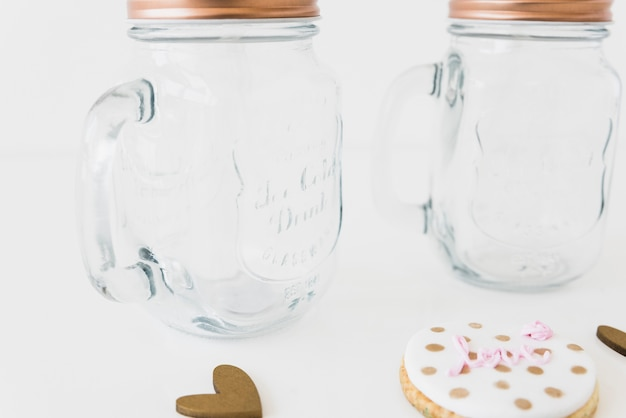 Delicious cookies and glass jar on white surface