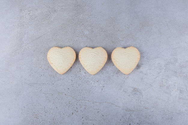 Delicious cookies in heart shaped placed on a stone table.
