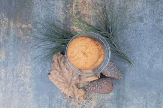 大理石の背景に葉と松ぼっくりとガラスの瓶においしいクッキー。高品質の写真
