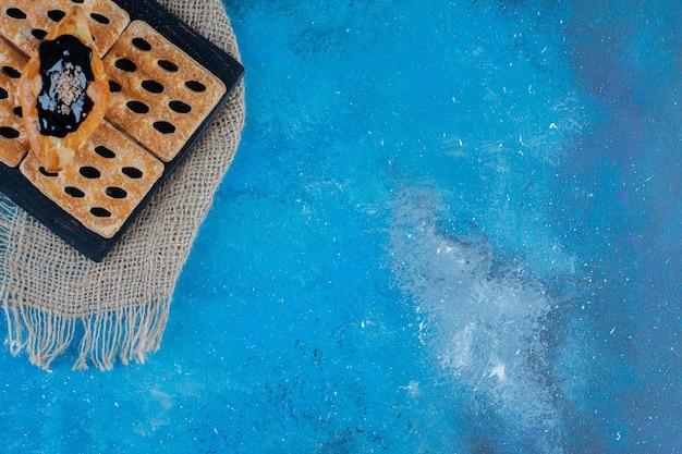 파란색 배경에 파란색 나무 보드에 맛있는 쿠키. 고품질 사진