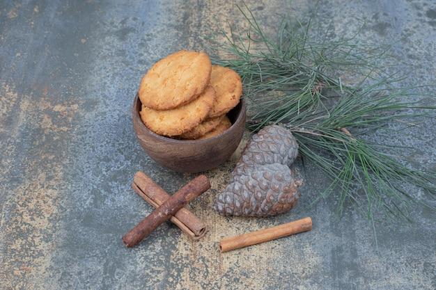 Вкусное печенье на деревянной миске с палочками корицы и шишками на мраморном столе.