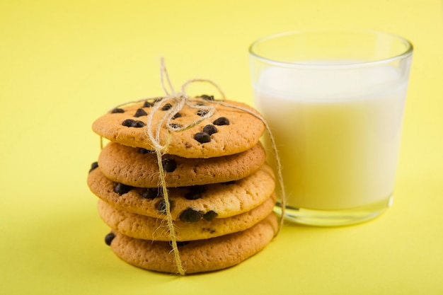 Delicious cookies with chocolate chips on a colored background