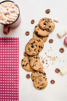 Delicious cookies with chocolate and hot drink with marshmallow on white table