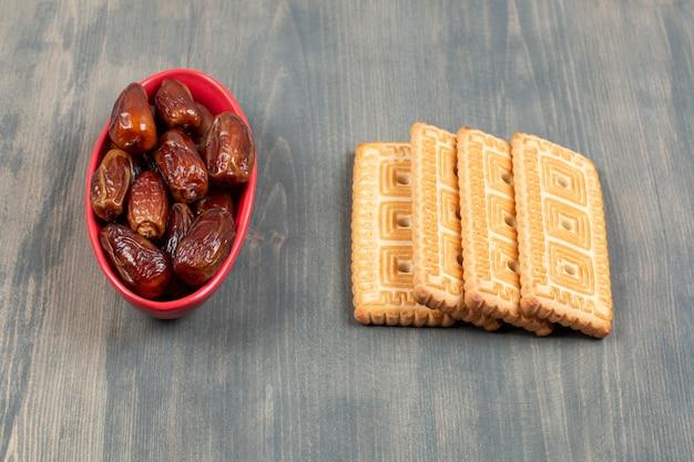 木製のテーブルに乾燥した日付のおいしいクッキー。高品質の写真