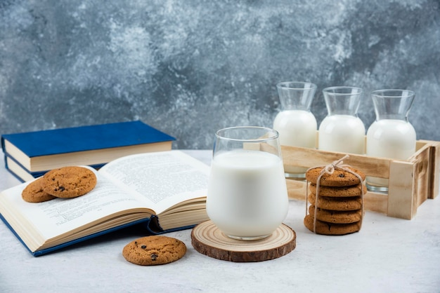 Delicious cookies with glass of milk and book.