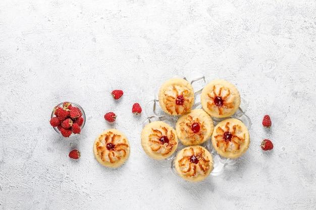 ラズベリージャムと新鮮なラズベリーのおいしいクッキー。