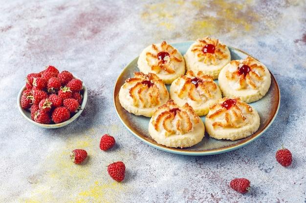 Deliziosi biscotti con marmellata di lamponi e lamponi freschi.