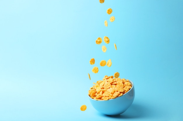 Delicious cornflakes falling into a plate on a colored background
