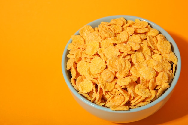 Delicious cornflakes in a plate against colored background