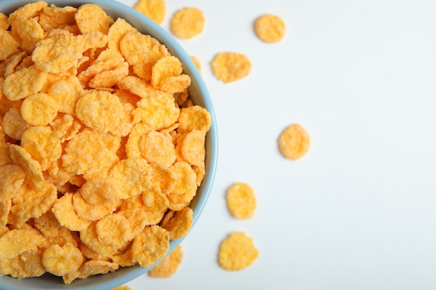 Delicious cornflakes in a plate on a light background