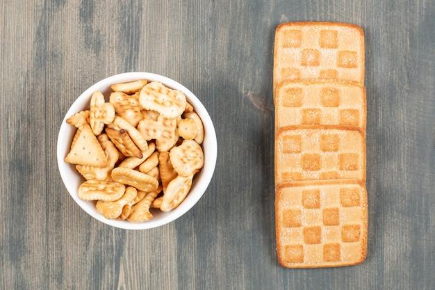 Deliziosi cracker e biscotti su piatti bianchi