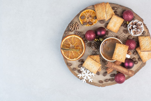 Delicious crackers and cup of coffee on wooden plate. high quality photo