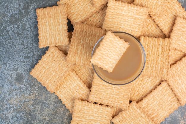 Deliziosi cracker con una tazza di caffè su sfondo di marmo. foto di alta qualità