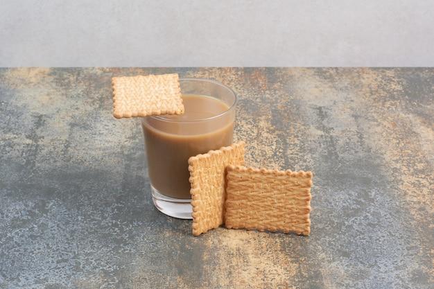 大理石の背景にコーヒーのカップとおいしいクラッカー。高品質の写真