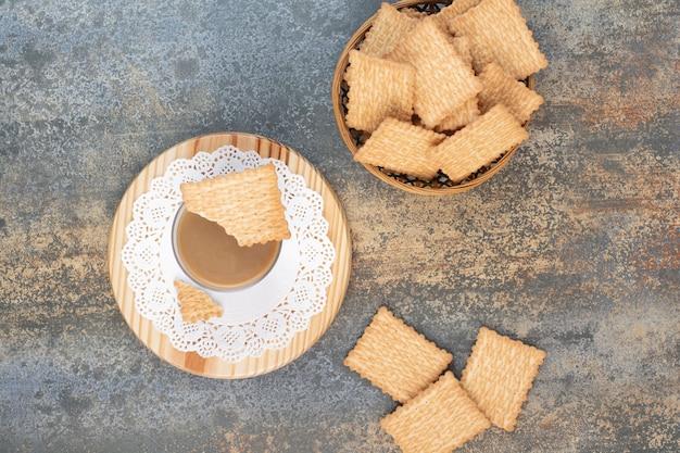 Deliziosi cracker in ciotola di legno su sfondo marmo. foto di alta qualità