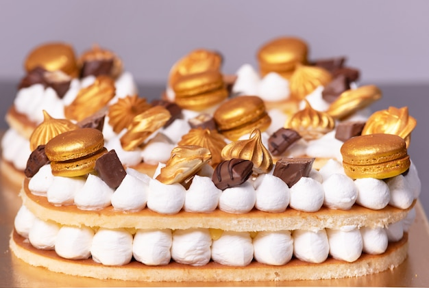 Delicious cream cake decorated with golden sweets.