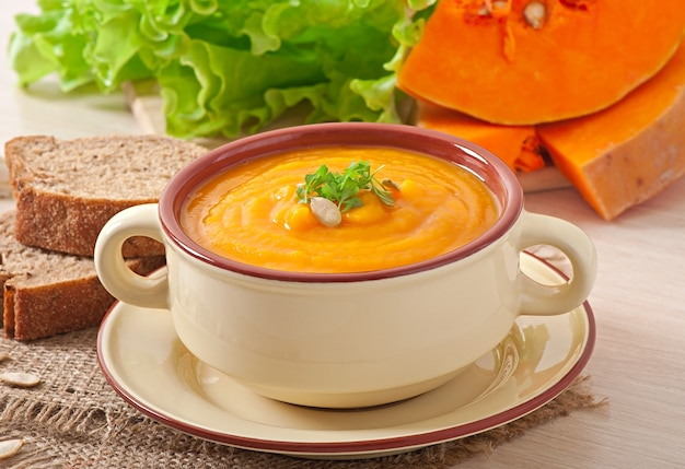 Delicious cream of pumpkin soup in a bowl on wooden table