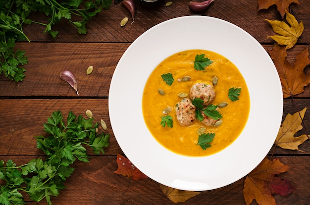 Delicious cream of pumpkin soup with meatballs made of turkey minced meat in a bowl on a wooden table.