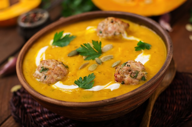 Delicious cream of pumpkin soup with meatballs made of turkey minced meat in a bowl on a wooden table
