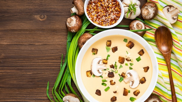 Delicious cream soup, made of mushrooms with croutons on a wooden table. top view. copy space.