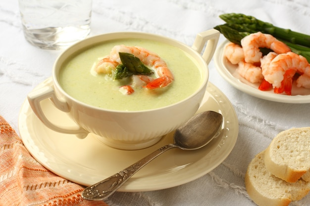 Delicious cream soup with asparagus and shrimp. selective focus