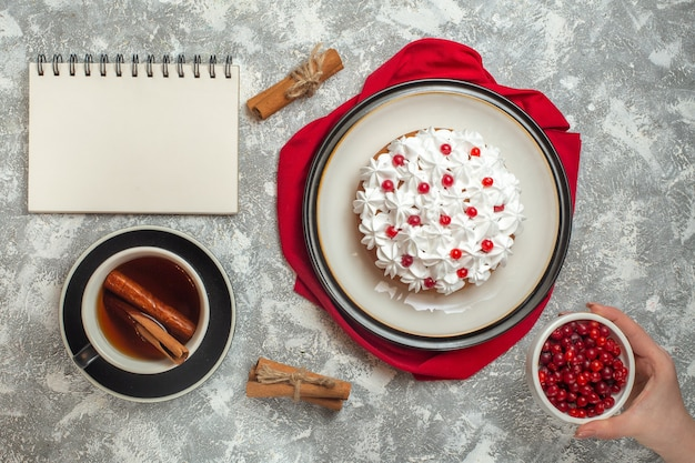 Delicious creamy cake decorated with fruits on a red towel and a cup of black tea