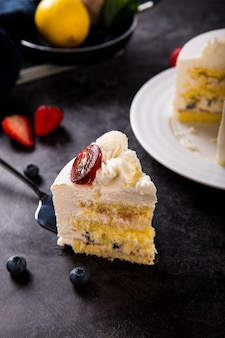 Delicious creamy cake with berries on luxury black table