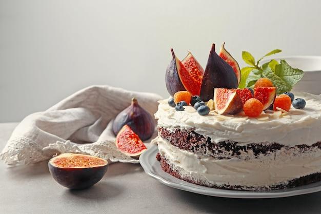 木製のテーブルにイチジクとベリーのおいしいクリーミーなケーキ
