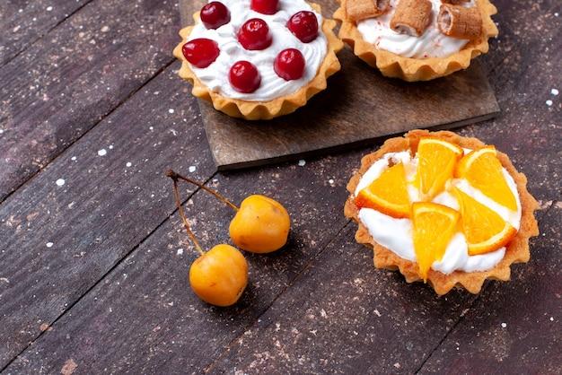 茶色の木製の茶色にスライスしたフルーツとおいしいクリーミーなケーキ、ケーキビスケットフルーツの甘い焼き