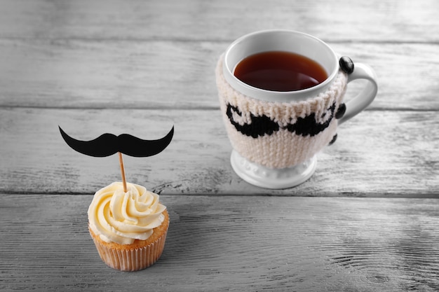 Delicious creative cupcake with mustache and cup of tea on wooden table