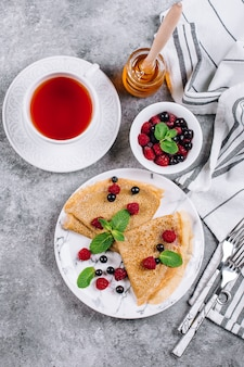 Delicious crepes breakfast on gray concrete table background. pancakes with berry