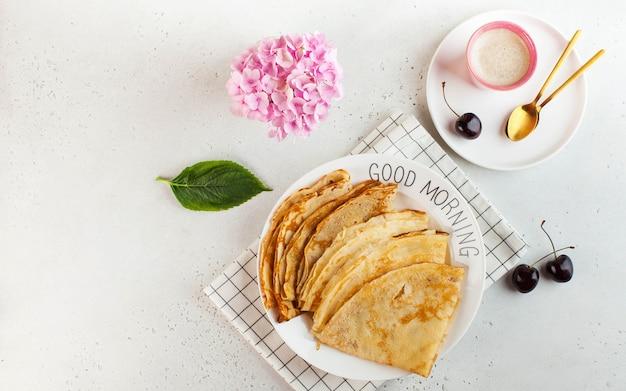 Вкусные блины на тарелках, кофейных кружках. концепция завтрака, десерт, рецепт, доброе утро.