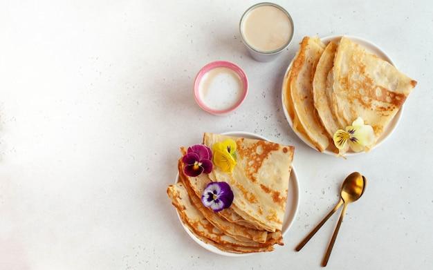꽃과 커피 머그잔으로 장식 된 접시에 맛있는 크레페