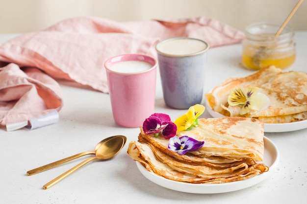 Delicious crepes on plates coffee mugs concept of breakfast dessert recipe french cuisine maslenitsa