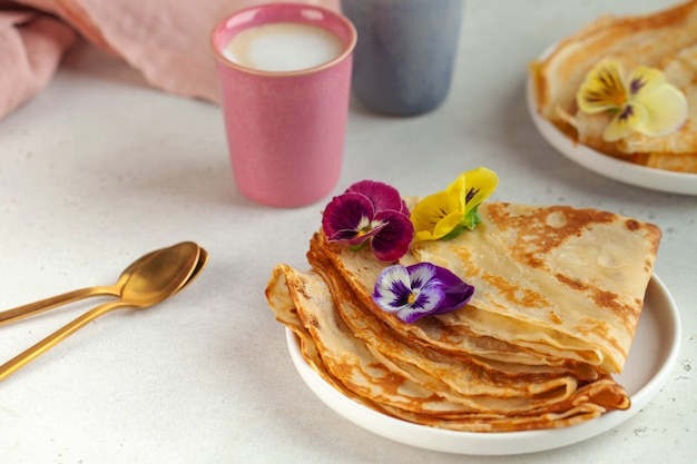 Delicious crepes on plates, decorated with flowers and coffee mugs