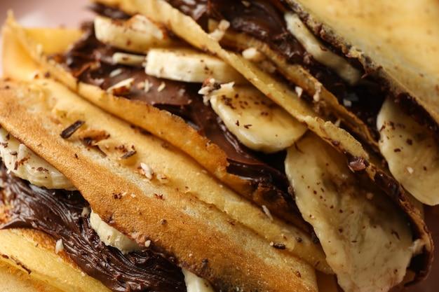 초콜릿 페이스트, 바나나, 견과류와 함께 맛있는 크레페를 닫습니다.