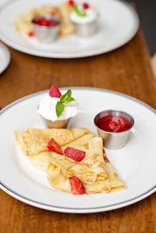 신선한 딸기, 민트 잎, 사워 크림 에스푸마를 곁들인 맛있는 크레페. 레스토랑에서 아침 식사. 부드러운 선택적 초점입니다.