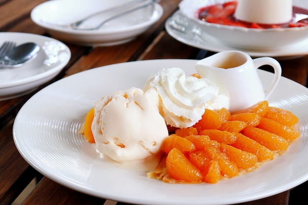 Delicious crepes with orange, ice cream, whipped cream and orange syrup on white plate