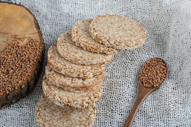 Delizioso pane croccante e cucchiaio di grano saraceno su tela bianca