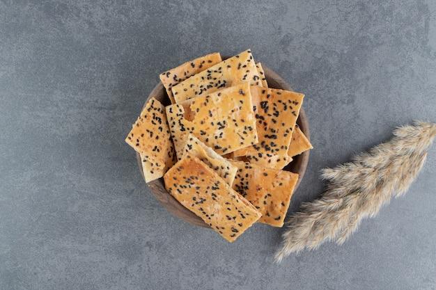 Deliziosi cracker croccanti con grano su una ciotola di legno