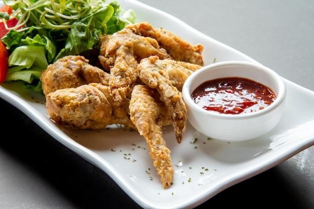 Вкусные хрустящие жареные куриные крылышки на белой тарелке с овощами и соусом из помидоров
