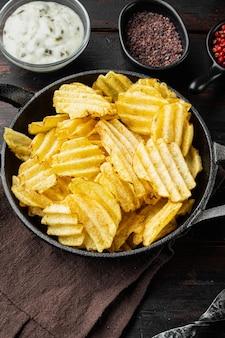 오래된 나무 테이블에 사워 크림과 함께 맛있는 바삭한 감자 칩 세트