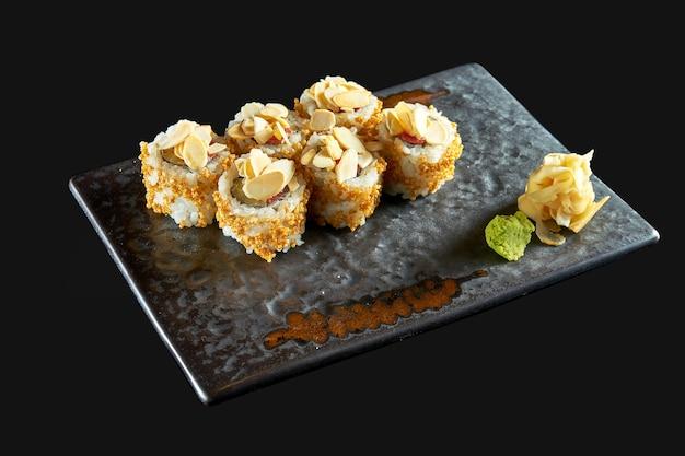 Вкусный хрустящий суши-ролл с тунцом, арахисом, попкорном и огурцом подается на керамической тарелке
