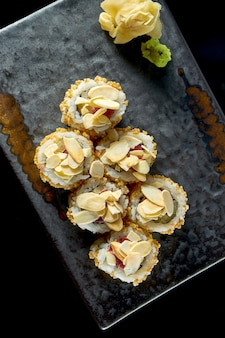 Delicious crispy sushi roll with tuna, peanuts, popcorn and cucumber, served on a ceramic plate with ginger and wasabi